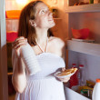 Pregnant woman looking for something in refrigerator — Foto Stock