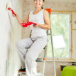 Woman paints wall with roller - Lizenzfreies Foto
