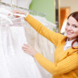 Pretty young bride choosing wedding dress — Photo