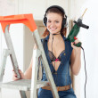 Sexy woman in headphones with drill — Stock Photo #23477903