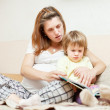 Mother and child reading  book together - Stock Photo