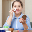 Foto Stock: Smiling mature womcleans make-up
