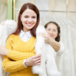 Female shop consultant helps girl chooses fur cape - Stok fotoğraf