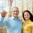 Happy couple against building new house   — Стоковая фотография