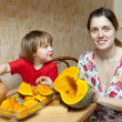 Mother with child cooks pumpkin - Stock Photo