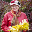 Stock Photo: Mature womwith maple posy