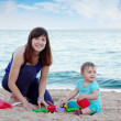 Happy mother with  toddler  on  beach — Stock Photo