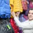 Stock Photo: Female buyer chooses winter jacket