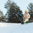 Woman doing downhill on sleigh - Stock Photo