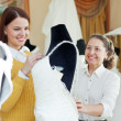 Shop assistant  helps to girl chooses white bridal outfit  — Stockfoto