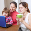 Happy women  of three generations looks netbook   — Stock Photo