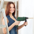 Happy girl in overalls drills hole — Stock Photo