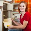 Woman defrosting the refrigerator — Stock Photo #23479257