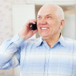 Happy mature man speaks by phone - Stock Photo