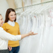 Shop assistant  helps bride in choosing  dress — Stockfoto