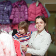 Girl with  mother chooses wear at  store - Stock Photo