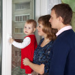 Parents with a child looking out the window — Stock Photo