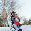 Women with child sliding on sleds — Stock Photo #23479951