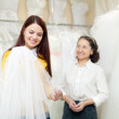 Girl chooses bridal veil at shop of wedding fashion — Zdjęcie stockowe