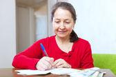 Mulher madura preenche documentos — Foto Stock