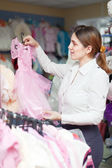 Woman chooses dress at children's clothes store — Stockfoto