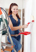Happy woman in overalls paints wall — Stock Photo