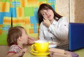 Businesswoman feeding baby and speak by mobile — Stock Photo