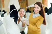 Kvinna hjälper bruden att välja brudklänning — Stockfoto