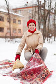 Girl in red cap cleans carpet with snow in winter day — Stock Photo