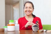 Mature woman puts facepowder — Stock Photo