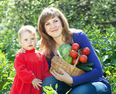 Happy woman and baby girl with vegetables — Stock Photo