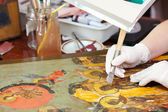 Restorer gilding on icon with agate burnisher — Stock Photo