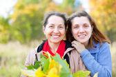 Happy women in autumn garden — Stock Photo