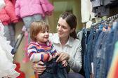 Glad kvinna och barn väljer jeans — Stockfoto