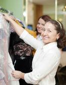Vrouwen kiest jurk bij shop — Stockfoto