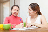 Daughter with mother fills in the questionnaire — Stock Photo