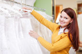Pretty young bride choosing wedding dress — Foto Stock