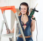 Sexy woman in headphones with drill — Stock Photo