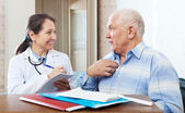 Senior man complaining to friendly doctor — Stock Photo