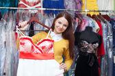 женщина выбирает вечернее платье в магазине — Стоковое фото