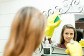 Smiling girl cleans mirror in bathroom — Stock Photo