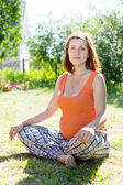 Pregnant woman sits on grass — Stock Photo