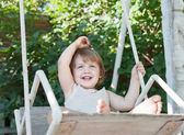Laughing girl on swing — Stock Photo