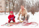 Woman with child cleans rug in winter day — Stock Photo