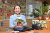 Saleswoman with flower at garden store — Stok fotoğraf