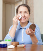 Smiling mature woman cleans the make-up — Stock Photo