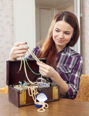 Pretty girl chooses jewelry in treasure chest — Stock Photo