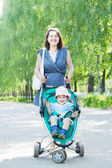 Mother with stroller in summer park — Stock Photo