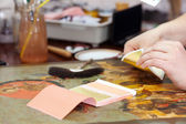 Restorer gilding on the old icon — Stock Photo