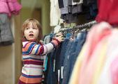 Niño elige los pantalones vaqueros en tienda — Foto de Stock